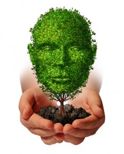 Nurture growth life development concept with a hand holding a green tree shaped as a front view human head as a caring metaphor and nature symbol for protection of the environment and growing potential.