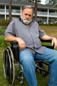 Disabled crippled man sits in his wheelchair in front of his home in the grass.